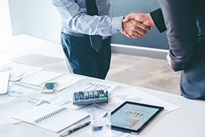 Two professionals shaking hands behind a white desk with a note pad, mobile device, pen and various investment charts.