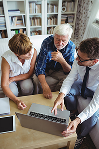 A Financial Advisor with a laptop meeting with a senior couple at their home.