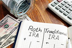 "Notebook open on table with ""Roth IRA"" and ""Traditional IRA"" Table Written on it"