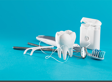 A tooth along with dental supplies including a toothbrush, dental floss and a mirror.