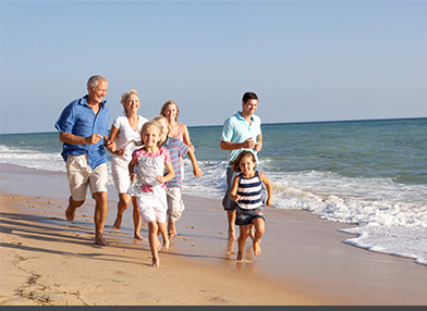 A family of generations running along the beach and ocean.