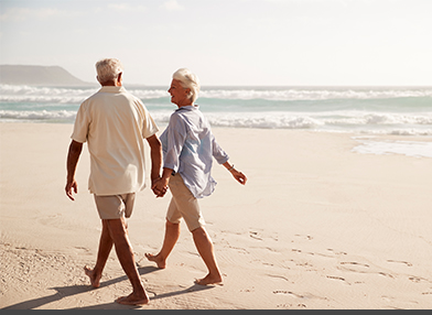 A retired couple walking on the beach near the ocean.