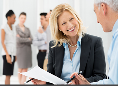 A Woman and Man discussing Retirement Plan paperwork with business colleagues in the background.