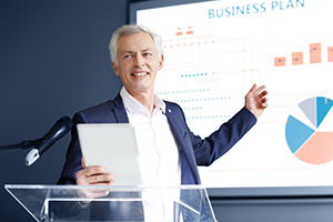 A business owner at a podium making a presentation pointing to a chart.