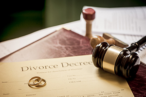 A Divorce Decree along with two rings and a gavel.