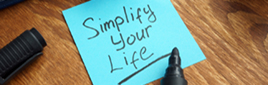 "Turquoise blue Post-it Note on tope of a wood desk with black sharpie marker text stating text ""Simplify Your Life""."